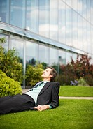 Businessman with eyes closed laying in grass outside office building