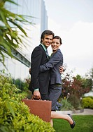 Smiling businessman and businesswoman hugging outside office building