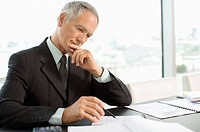 Focused businessman reading paperwork in office