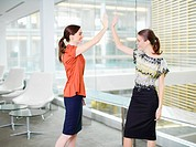 Smiling businesswomen giving high five in office