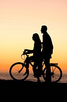 Teenage couple at the beach with bicycle at sunset