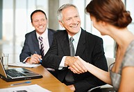 Smiling business people shaking hands in conference room