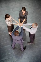 Business people standing in circle with hands stacked
