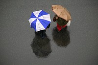 USA, New York City: overhead view of two people with umbrellas crossing street