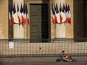 Couple sits on ground in front of French Tri_Color flags hanging from the columns of the Pantheon, Paris, France