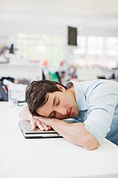 Businessman sleeping on laptop at desk in office