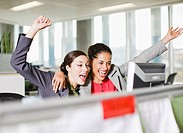Excited businesswomen with arms raised looking at computer in office