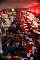 Aerial of shoppers using multiple checkout aisles in a crowded grocery store.