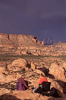 Two People Camping Beneath Storm Clouds Near Moab, Utah