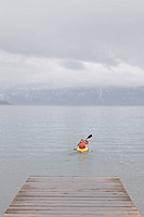A man kayaking on Lake Tahoe in the fog in winter.