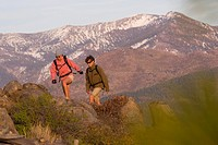 A man and woman hiking in the fall with the snowy Sierra mountains in the background.