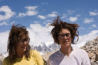 Two smiling dorky women with messy hair on the Biafo Glacier in the Karakoram Himalya in Pakistan