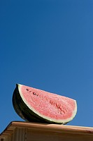 Slice of watermelon against blue sky