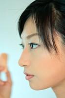 A young woman applying makeup, close_up