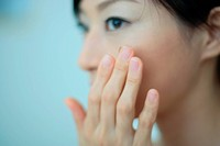 Close_up of a young woman putting moisturizer to face