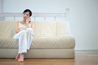 A young woman talking over phone sitting in sofa