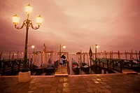 Couple embracing on waterfront near St Marks Square in Venice at dusk