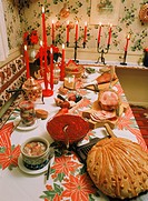 Swedish Christmas table or julbord with cheese, baked bread, beats, aquavit, roast ham, marinated herring and candles