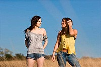 USA, Texas, two teenage girls standing in field