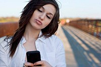 Teenage girl using mobile phone on bridge