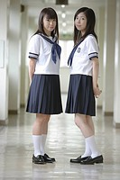 Two high school girls standing in school corridor