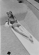 Young woman in swimwear lying on diving board