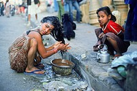 Young girl washing hair using pots of water on streets of Katmandu in Nepal