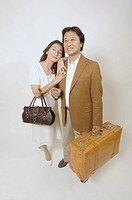 Mature couple standing with suitcase and bag