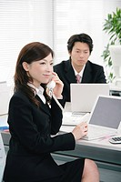 Young woman and mid adult man working in office
