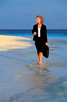 Business woman with briefcase walking to work along sandy shore at sunrise