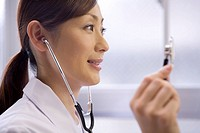 A female doctor examining patient with stethoscope