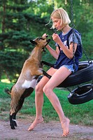Girl playing with pet goat in countryside home yard