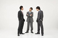 Three businessmen glaring at each other