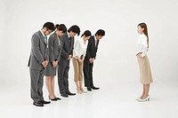 Business people bowing to businesswoman