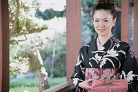 Young woman in kimono holding wrapped gift