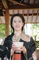 Young woman in kimono holding tea cup