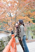 Two young women standing on bridge at Ohara Sanzenin Temple, Kyoto Prefecture, Japan