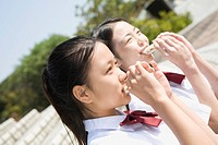 Two schoolgirls eating sandwiches