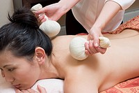 Young woman receiving herbal ball massage
