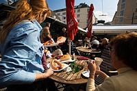 Austria, Vienna, local people having food at Naschmarkt in Linke Wienzeile