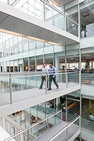 England, West Midlands, Birmingham. Two businessmen walking between offices in the central atrium at 4 Brindleyplace.