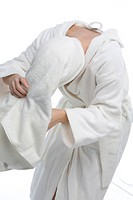 Woman in bathrobe wrapping a towel around her head