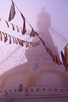 NEPAL, KATHMANDU, BOUDHNATH, TIBETAN STUPA TEMPLE IN FOG, PRAYER FLAGS, PIGEONS