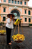 VIETNAM, SAIGON HO CHI MINH CITY, CENTRAL POST OFFICE, FRENCH COLONIAL STYLE, WOMAN SELLING BANANAS, NON LA CONE HAT