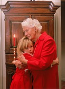 Granddaughter hugging grandmother at home