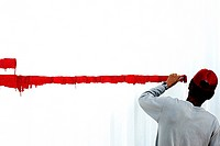 Rear view of a man painting a red line on a white wall