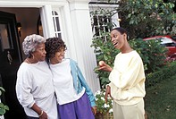 Three generations of afro american women in front of their house
