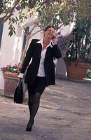 Businesswoman walking outdoors and talking on mobile