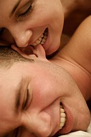Young woman nibbling on a man´s ear