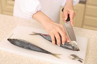 Human Hand cutting fish